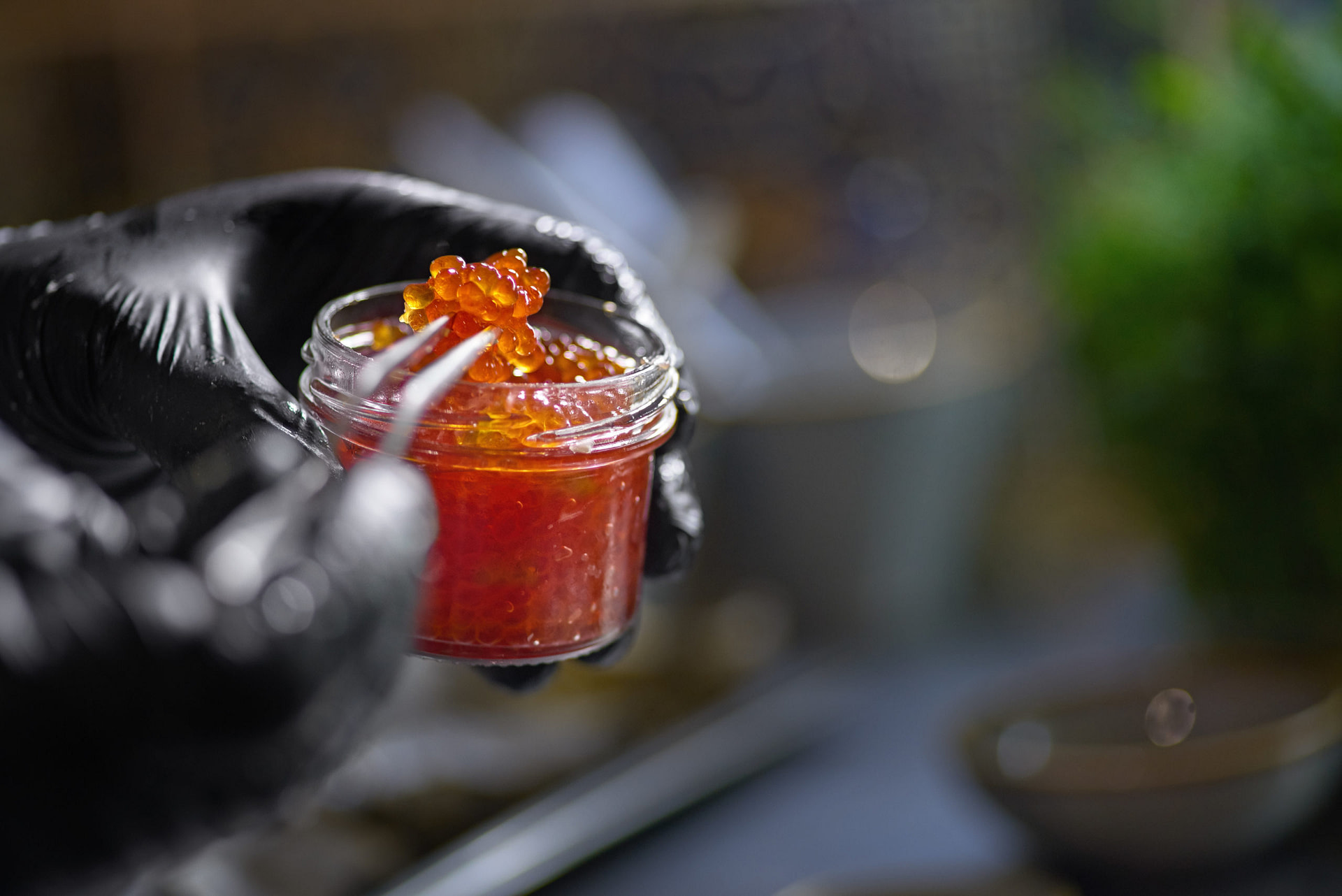 Food concept. The chef picks red caviar from a jar with tweezers. Selective focus. Shallow depth of field. The process of making spaghetti with seafood.